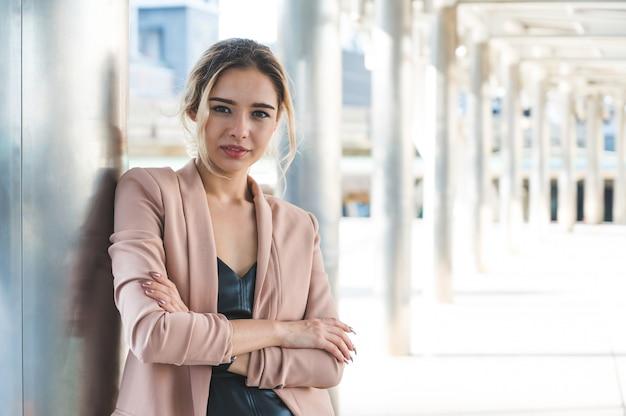 Porträt der lächelnden hübschen jungen geschäftsfrau mit verschränkten armen auf bürohintergrund.