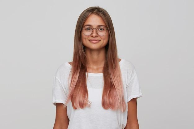 Porträt der lächelnden hübschen jungen studentin mit langen gefärbten pastellrosa haaren trägt t-shirt und brille fühlt sich glücklich und zuversichtlich isoliert über weiße wand sieht nach vorne
