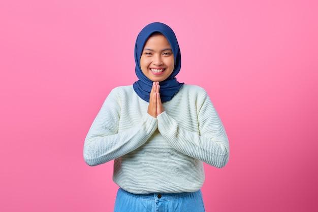Porträt der lächelnden jungen asiatischen frau, die betende geste auf rosa hintergrund zeigt