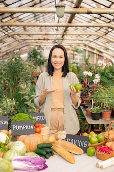 Porträt der lächelnden jungen asiatischen frau im hemd, das über frische äpfel am bauernmarkt erzählt