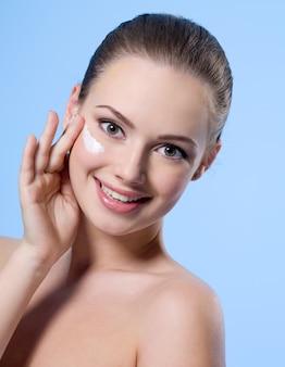 Porträt der lächelnden jungen beauitufl frau, die creme auf ihrem gesicht aufträgt - blauer raum