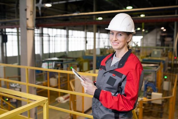 Porträt der lächelnden jungen dame im helm und in der arbeitskleidung, die auf fabrikbrücke stehen und figuren auf tablette analysieren