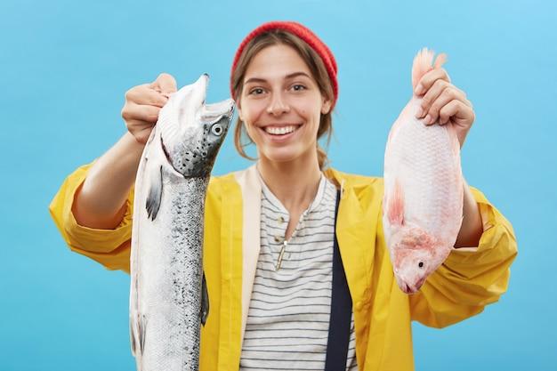 Porträt der lächelnden jungen fischerin, die vom angelausflug kommt