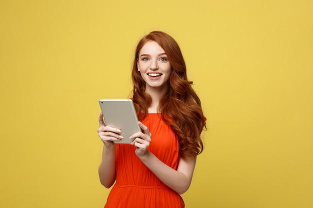 Porträt der lächelnden jungen frau der reizenden rothaarigen mit dem arbeiten an tablette