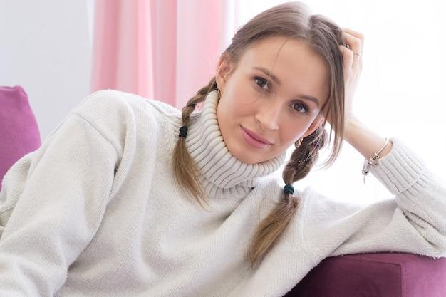 Porträt der lächelnden jungen frau, die auf couch sitzt, genießen wochenende in gemütlichem haus