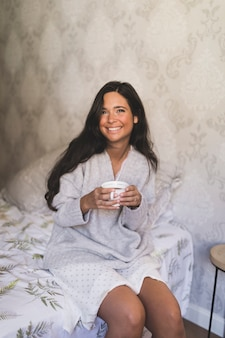 Porträt der lächelnden jungen frau, die auf dem bett hält kaffeetasse sitzt