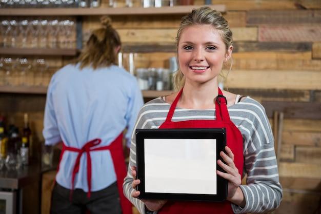 Porträt der lächelnden jungen frau, die digitales tablett mit männlichem kollegen im hintergrund am kaffeehaus zeigt