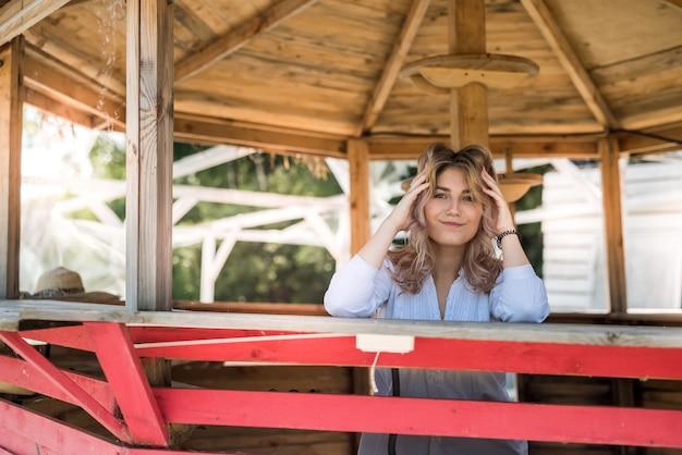 Porträt der lächelnden jungen frau, die ferienzeit genießt, nahe sandstrand im hölzernen pavillon.