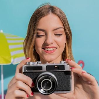 Porträt der lächelnden jungen frau, die fotos auf kamera macht