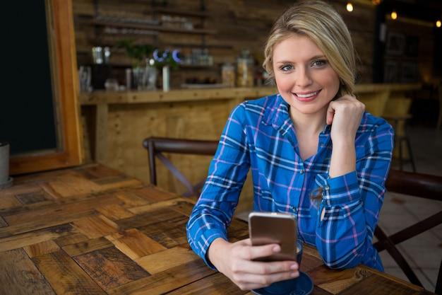 Porträt der lächelnden jungen frau, die handy am tisch im kaffeehaus verwendet