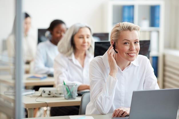 Porträt der lächelnden jungen frau, die headset trägt und beim arbeiten als call-center-betreiber schaut