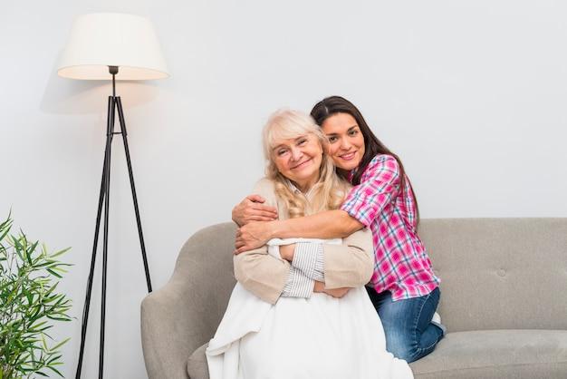 Porträt der lächelnden jungen frau, die ihre ältere mutter sitzt auf sofa umfasst