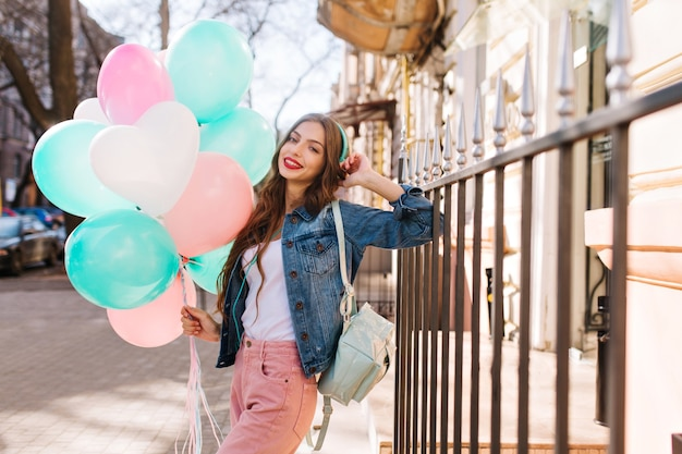 Porträt der lächelnden jungen frau, die jeansjacke und stilvolle hosen trägt, die mit geburtstagsballons aufwerfen.