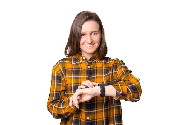 Porträt der lächelnden jungen frau, die kamera betrachtet und einen finger auf die smartwatch drückt