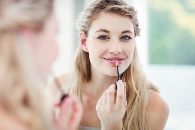 Porträt der lächelnden jungen frau, die lipgloss anwendet