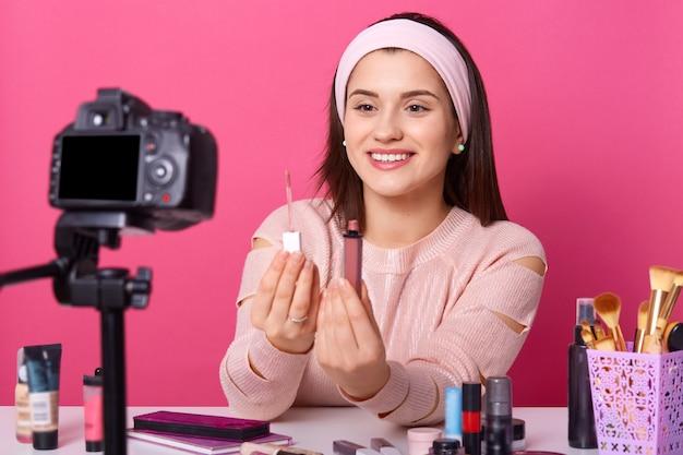 Porträt der lächelnden jungen frau, die lippenstift zur kamera zeigt