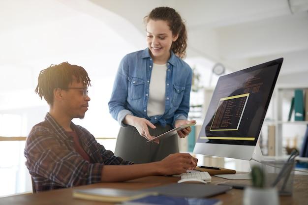 Porträt der lächelnden jungen frau, die mit afroamerikanischem mann spricht, der code schreibt, während sie in der softwareentwicklungsagentur arbeitet, kopiert raum