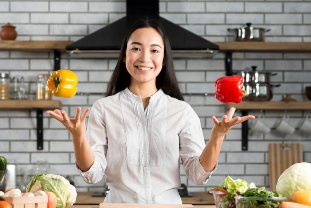 Porträt der lächelnden jungen frau, die mit grünem pfeffer in der küche jongliert