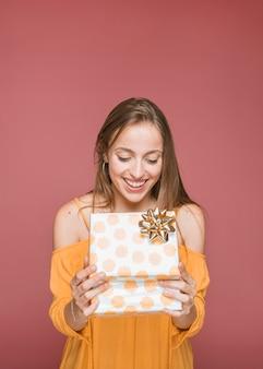 Porträt der lächelnden jungen frau, die offene geschenkbox betrachtet