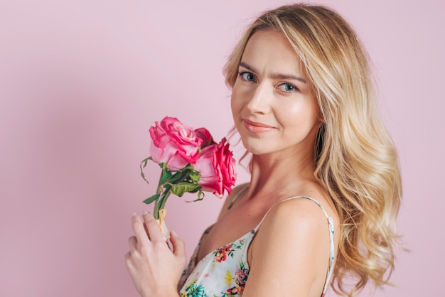 Porträt der lächelnden jungen frau, die rosa rosen gegen rosa hintergrund hält