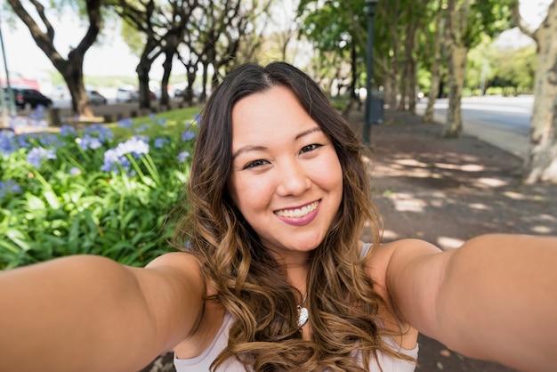 Porträt der lächelnden jungen frau, die selfie im park nimmt