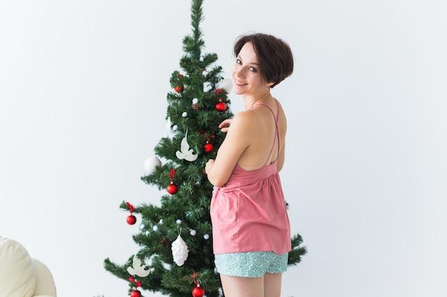 Porträt der lächelnden jungen frau, die weihnachtsbaum verziert.