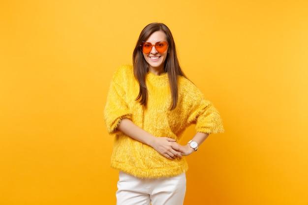Porträt der lächelnden jungen frau im pelzpullover, in der weißen hose und in der orangefarbenen brille des herzens, die lokalisiert auf hellgelbem hintergrund steht. menschen aufrichtige emotionen, lifestyle-konzept. werbefläche.