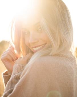 Porträt der lächelnden jungen frau im sonnenlicht, die kamera betrachtet