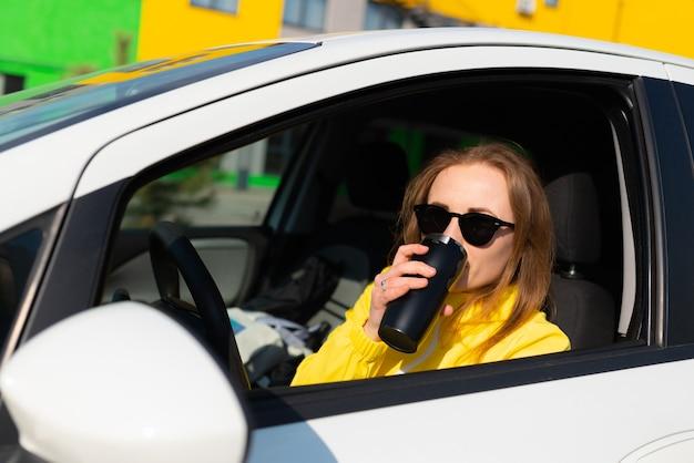 Porträt der lächelnden jungen frau in einer gelben jacke, die eine kaffeepause in ihrem auto hat.