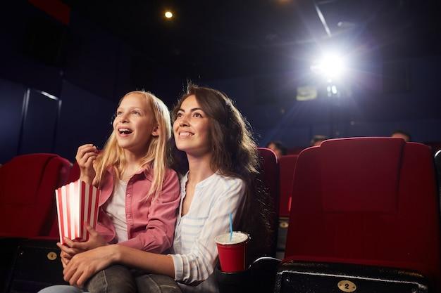 Porträt der lächelnden jungen frau mit der niedlichen tochter, die zeichentrickfilme im kino beobachtet, während sie auf bildschirm schaut und popcorn genießt, kopieren raum
