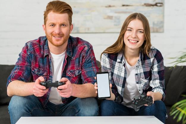 Porträt der lächelnden jungen frau, welche die steuerknüppel in der hand hält, sitzend mit ihrem freund, der mobilen schirm zeigt