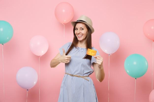 Porträt der lächelnden jungen glücklichen frau im blauen kleid des strohsommerhuts, das kreditkarte hält, die daumen auf rosa hintergrund mit bunten luftballons zeigt. geburtstagsfeier-partyleute aufrichtige gefühle.