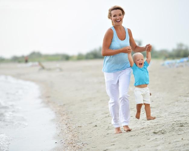 Porträt der lächelnden jungen mutter mit dem kleinen kind, das auf dem strand läuft.