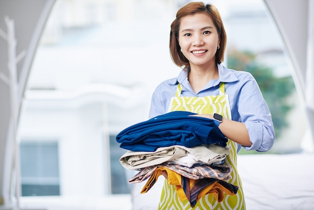 Porträt der lächelnden jungen vietnamesischen hausfrau, die stapel gewaschener und trockener kleidung hält