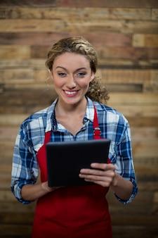 Porträt der lächelnden kellnerin unter verwendung der digitalen tablette gegen holzwand