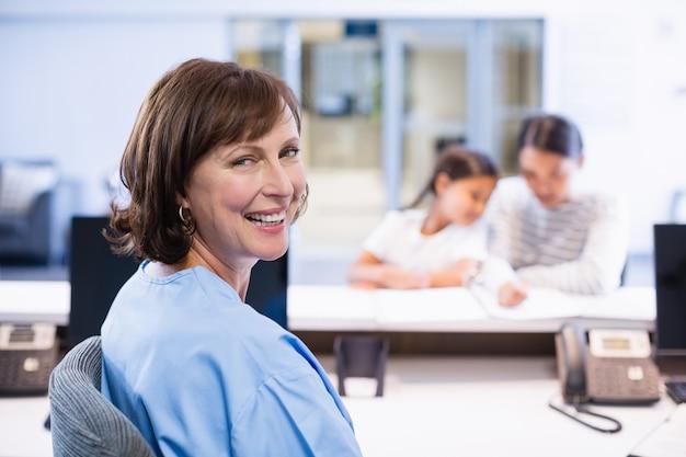 Porträt der lächelnden krankenschwester, die am schreibtisch sitzt
