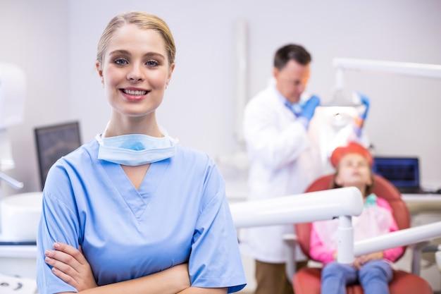 Porträt der lächelnden krankenschwester mit verschränkten armen