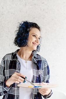 Porträt der lächelnden künstlerin, die ölfarben auf palette setzt, die in ihrem studio arbeitet