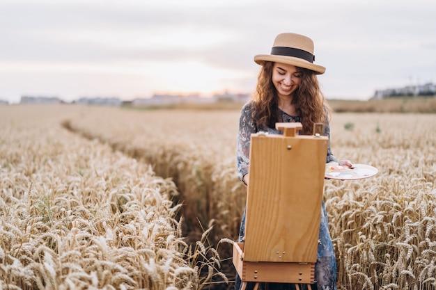 Porträt der lächelnden künstlerin mit dem lockigen haar im hut. mädchen zeichnet ein bild einer landschaft in einem weizenfeld. speicherplatz kopieren