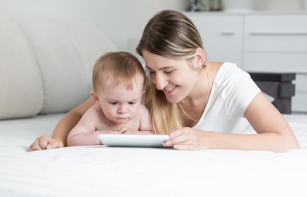 Porträt der lächelnden mutter und des babys mit tablet-pc als auf dem bett liegend