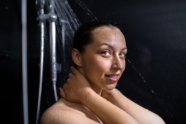 Porträt der lächelnden nackten jungen frau, die fließendes wasser genießt, dusche nimmt, im badezimmer steht und hände am hals hält und sich um ihre haut an der schwarzen wand kümmert