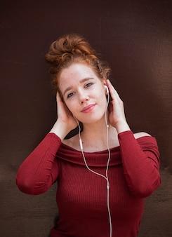Porträt der lächelnden rothaarigefrau, die musik hört