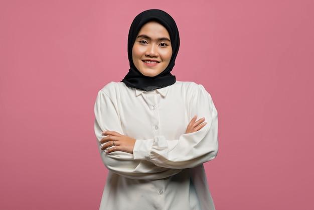 Porträt der lächelnden schönen asiatischen frau, die ein weißes hemd mit gefalteter hand trägt