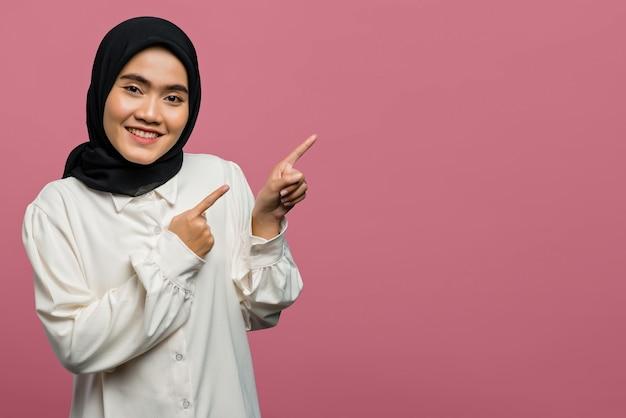 Porträt der lächelnden schönen asiatischen frau, die mit dem finger auf leeren raum zeigt