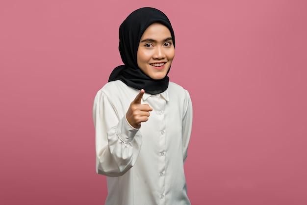 Porträt der lächelnden schönen asiatischen frau, die mit dem finger nach vorne zeigt