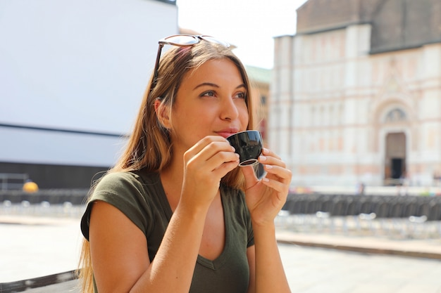 Porträt der lächelnden schönen frau, die im freiencafé in italien sitzt und kaffee trinkt