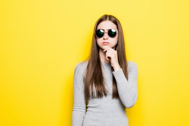 Porträt der lächelnden schönen frau in der sonnenbrille und im kleid gegen die gelbe wand