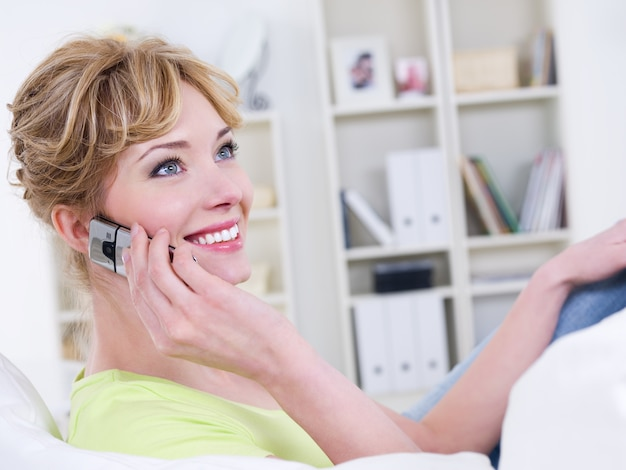 Porträt der lächelnden schönen fröhlichen frau mit dem mobilen sprechen - drinnen