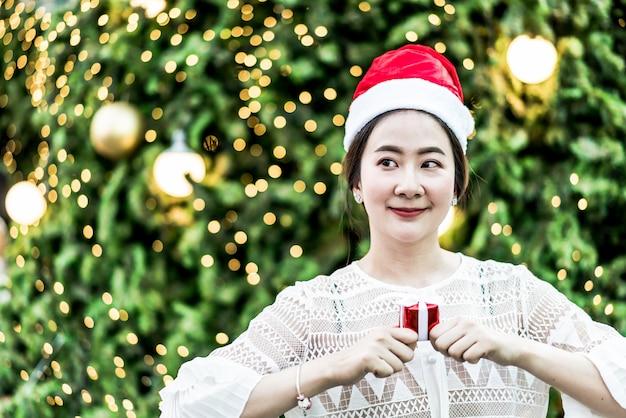 Porträt der lächelnden schönen jungen asiatischen frau mit geschenk auf dem festlichen weihnachtsmarkt