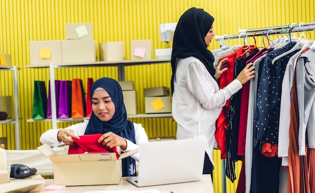 Porträt der lächelnden schönen zwei muslimischen besitzerin asiatische frau freiberufliche sme geschäft online-shopping arbeiten auf laptop-computer mit paketbox auf tisch zu hause - geschäft online-versand und lieferung
